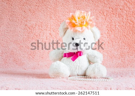 White teddy bear toy with orange flower barrette on head sitting on pink terry background