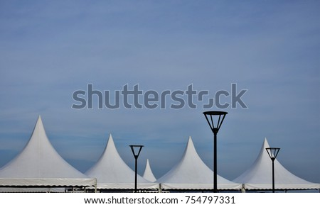 White tents and pillars of street lamps against the sky, abstract background. #754797331