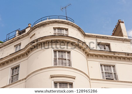 White terrace house in London. Terraced houses is a style of medium-density housing that originated in Europe in the 16th century, where a row of identical or mirror-image houses share side walls.