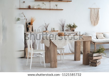 White textured kitchen in the style of shabby. A large table in an ecological style and loft style. Rustic shelves, napkins, old refrigerator, diy