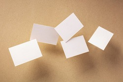 White thick business cards, flying on a brown paper background, a mock-up for a creative design presentation