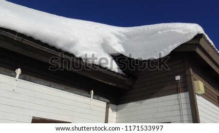 White Thick snow dritf on roof of hut, lot of icy snow fall down #1171533997