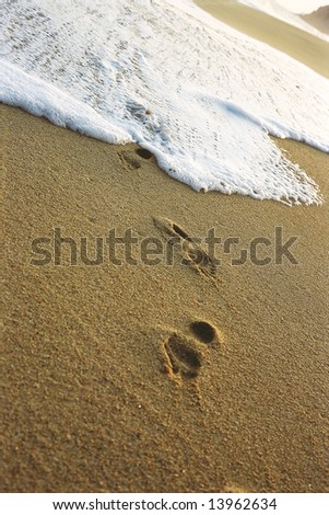 White tide washing over a foot print covered beach.