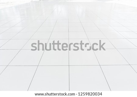White tile floor clean and symmetry with grid line texture in perspective view for background. Flooring permanent covering by tile, Square shape of white tile made from ceramic material covering floor