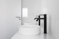 White tiled bathroom with two wash basins and black faucets.