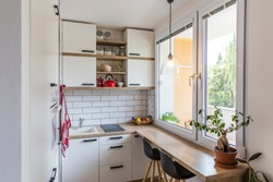 White tiny modern kitchen with red components, reconstruction, cosy small panel house in Prague, Czech Republic