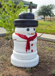 White tire snowman with a black tire hat, red scarf and stick arms.