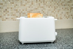 White toaster with toasted bread for breakfast inside. Gray table
