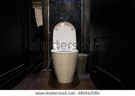 white toilet in black restroom with toilet paper #680462086