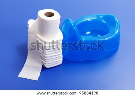 White toilet paper and  stack of diapers beside blue potty on blue background