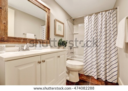 White tones Bathroom with vanity cabinet and wooden framed mirror. Decorated with picture, plant pot and striped curtain. Northwest, USA