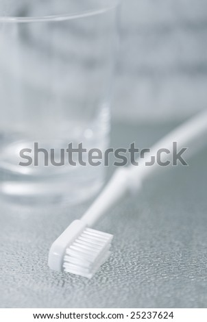 White toothbrush and a glass, very short depth of field