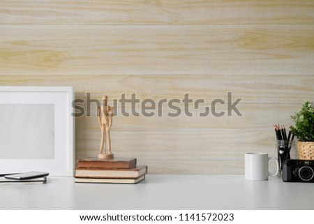 White top desk and wooden wall with book, coffee cup and artist accessories with copy space. workspace and designer accessories.