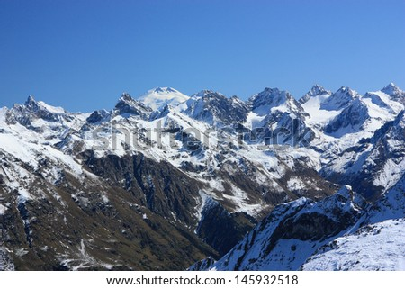 White tops of the mountains slopes above the yellow in the autumn season