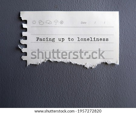 White torn note stick on gray wall with text typed FACING UP TOO LONELINESS - concept of accept and embrace loneliness, facing up to living alone , become more at peace and content Stockfoto ©