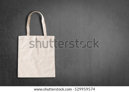 White tote bag canvas fabric cloth eco shopping sack mockup isolated on blackboard background with copyspace