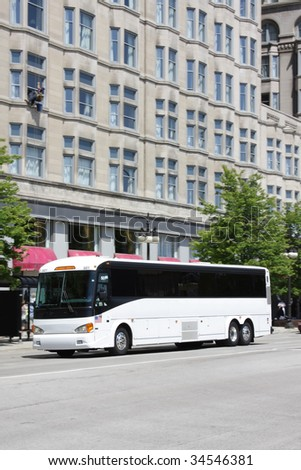 White tour bus in a downtown city area