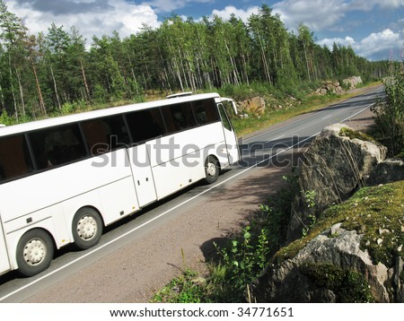 white tourist bus on rural highway, slightly blurred in motion