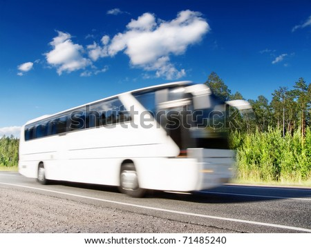 white tourist bus speeding on highway, blured in motion - stock photo