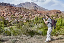 White tourist in a disposable medical mask as a protection in a period of coronavirus pandemic infection covid-19 is making photos in Abyaneh near Kashan, Iran.