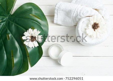 white towel, leaf of a palm tree, decorative cosmetics on a light background top view, spa
