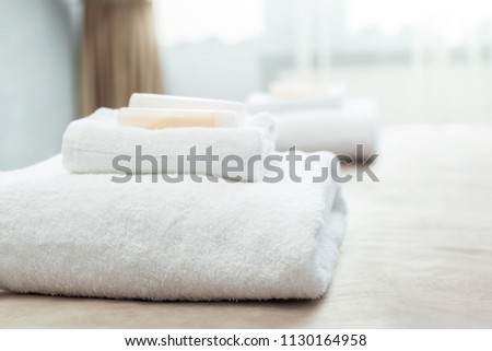 White towel on bed in guest room for hotel customer #1130164958