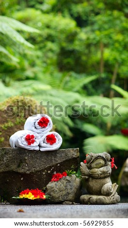 White towels and red hibiscus flowers in tropical spa in Bali
