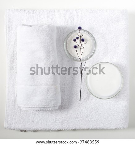 White towels, bath salt and body cream on a white background