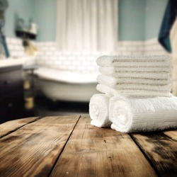 white towels in bathroom and free space on retro table for you in vintage bathroom