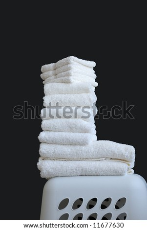 White Towels On Black - a stack of white folded towels and wash clothes sitting on top of a plastic laundry basket.  Black background with copy space.