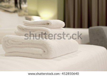 white towels rolled and piled on bed #452850640