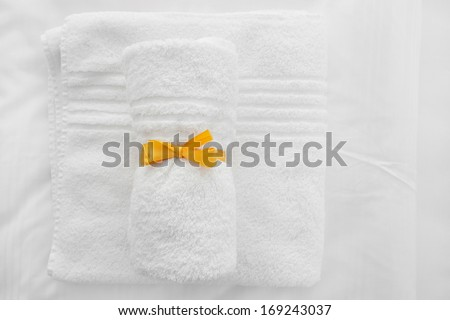 White towels with yellow ribbon folded on white sheets.