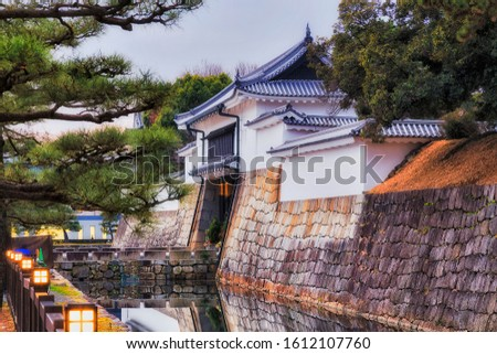 WHite tower and entrance gate to Nijo caste in Kyoto city - historic castle of local Shogun - present park, garden and heritage site surrounded by stone walls and water filled moat in Japan.