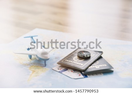 White toy airplane; compass on passports and baggage allowances card on map against wooden table #1457790953