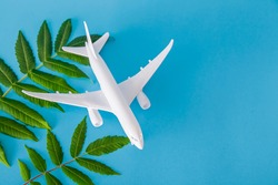 White toy plane with green plant on blue background, environmental protection concept. Clean fuel concept