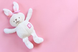 White toy rabbit on isolated pink background. Top view of easter rabbit with copy space. Happy easter concept.
