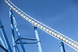white tracks of steel roller coaster with blue steel supporting tubular against blue sky