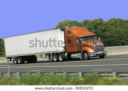 White trailer truck with orange cab against blue sky. Plenty of copy space.
