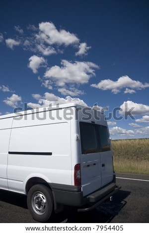 White transit van against a blue sky background