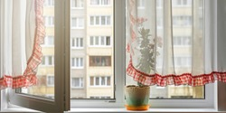 white transparent curtain with red edge hanging on plastic window with open frame and flowerpot on window sill building background