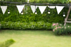 white triangle flags and light bulbs decorate in garden. concept : outdoor party.