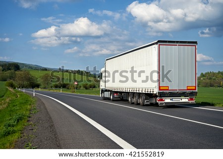 White truck departing on an asphalt road meander trough the green fields. Warning traffic sign Bend to right. Wooded mountains in the background. Sunny spring day with blue skies and white clouds.