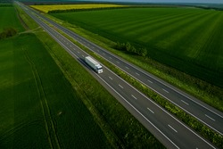 white truck driving on asphalt road along the green fields. seen from the air. Aerial view landscape. drone photography.  cargo delivery . cargo delivery and transportation concept