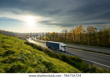 White truck driving on the highway turning towards the horizon in an autumn landscape with sun shining through the clouds in the sky #786756724