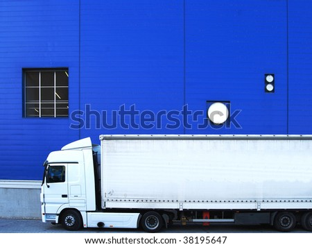 White truck in front of an industrial building with blue cladding