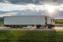 White truck is on highway - business, commercial, cargo transportation concept, beautiful sunset sky, clear and blank space - side view