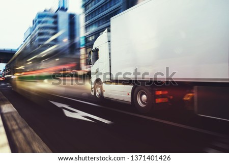 White truck moving fast on the road in a modern city with light effect