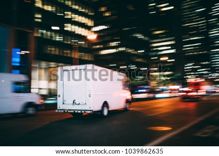White truck of logistic shipping company on city road delivering goods for order quickly in time, truck moving speedily on avenue transporting and distributing stuff for postal service in metropolis #1039862635