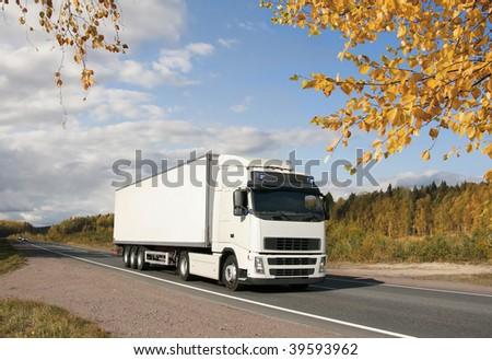 white truck on golden autumn highway, landscape