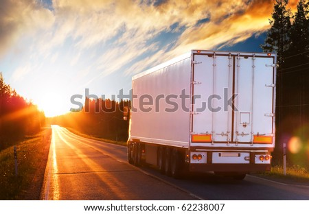 White truck on the asphalt rural road in the polar night - stock photo